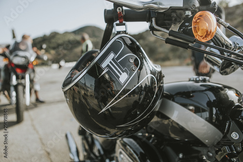 Fototapety, obrazy: Close up of black helmet hanging from a classic black motorcycle handlebar.