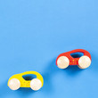 Two Wooden Toy Cars on Blue Background