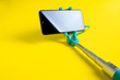 canvas print picture - Monopod for selfie with smart phone. Selfie stick with smartphone isolated on yellow background