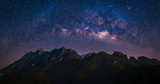 Fototapeta Kosmos - Night view of nature mountain with universe space of milky way galaxy and stars on sky
