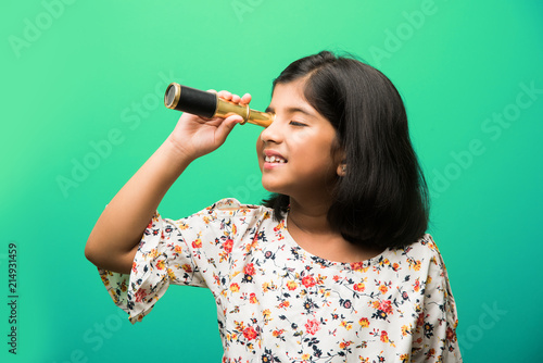 Cute little Indian/asian girl using stretch telescope and looking up in the sky, want to be a scientist. Standing isolated over white or green chalkboard background