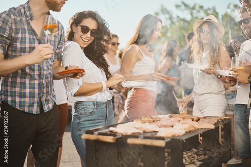Group of people standing around grill, chatting, drinking and eating.