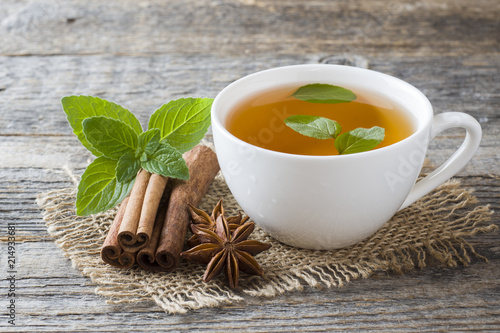 Staande foto Thee Cup of tea with fresh mint leaves and cinnamon anise on a wooden background. Copy space.