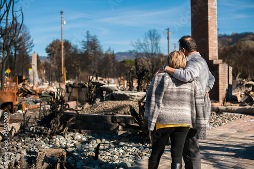 Man and his wife owners, checking burned and ruined of their house and yard after fire, consequences of fire disaster accident Fotobehang
