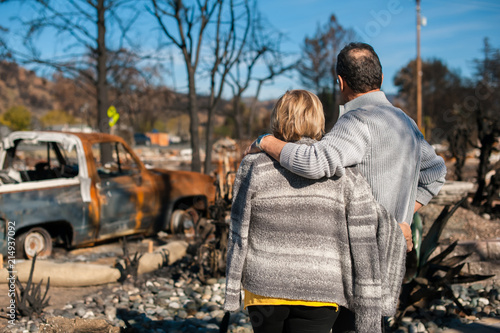 Man and his wife owners, checking burned and ruined of their house and yard after fire, consequences of fire disaster accident Wallpaper Mural