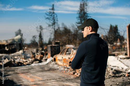 Fotomural Man owner checking burned and ruined house and yard after fire, consequences of fire disaster accident
