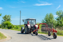 Tractor With Hay Tedder On Rural Road On Sunny Day