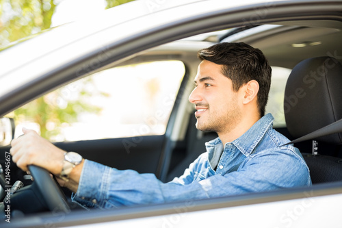 Fotografering Good looking guy driving a car