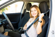 Woman putting her seat belt before driving