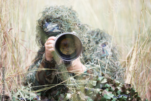 Fotografering Photographer in ghillie suit hiding in forest to take wildlife photo for educati