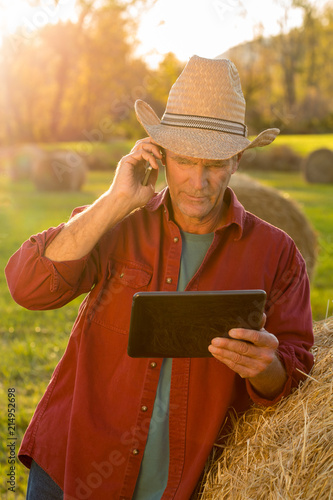 Farmer using tablet and talking on mobile phone Poster