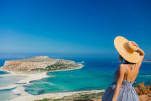 Young Redhead Girl In Hat And Dress With Sea Coastline On Balos, Crete, Greece