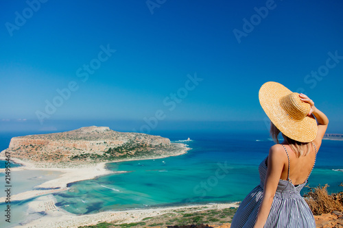 Stampa su Tela Young redhead girl in hat and dress with sea coastline on Balos, Crete, Greece