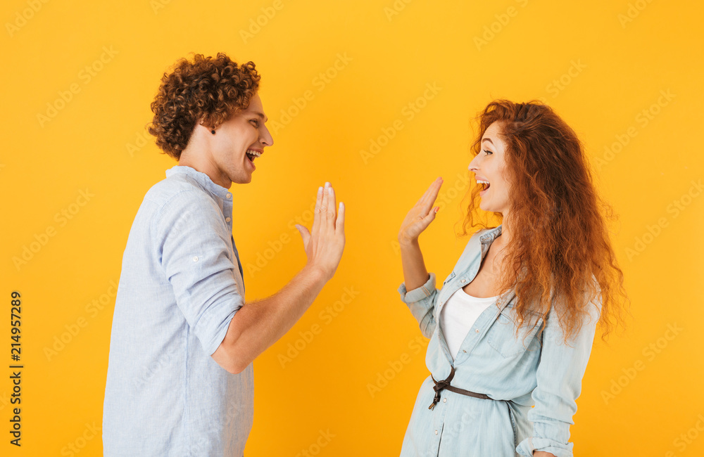 Fototapety, obrazy: Photo of joyful couple man and woman standing face to face and giving high five, isolated over yellow background