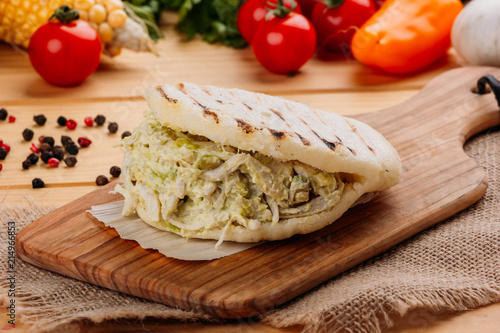 Famous and delicious Venezuelan AREPA called Reina Pepeada on a kitchen board