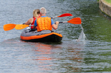 Man And Woman Paddling In Unis...