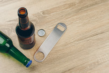 Two Bottles Of Beer And A Stainless Steel Bottle Opener Or Bar Blade On Wooden Table
