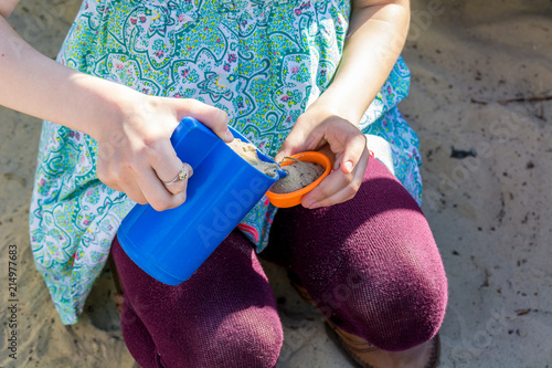 Girl in maroon tights plays with toys in a sandbox