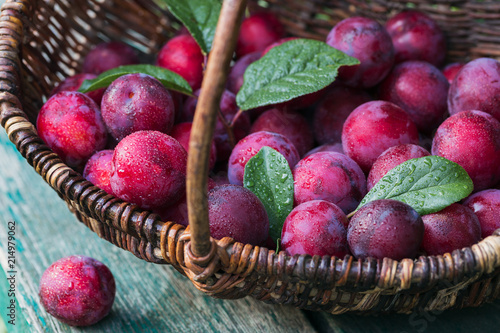 Fresh plums with leaves on rustic wooden table background.