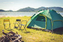 Camping Tent With Extinguished Bonfire In The Green Field Meadow, Lake And Mountain Background. Picnic And Travel Concept. Nature Theme.