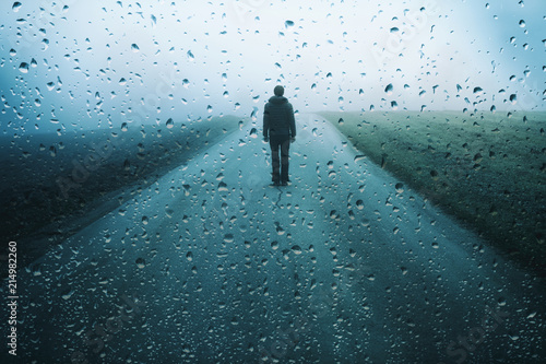 Leinwand Poster Lonely man stands on misty road with artistic raindrops background