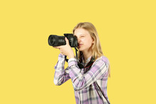 Young Teenage Girl Holding Digital Photo Camera With Big Lens & Strap, Taking Pictures, Smiling. Beautiful Blond Female Photographer In Checkered Plaid Shirt Posing W/ Dslr Gear. Copy Space Background