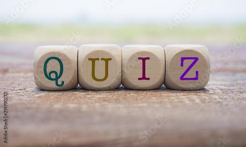 Fototapety, obrazy: Quiz word written on cube shape wooden blocks on wooden table.