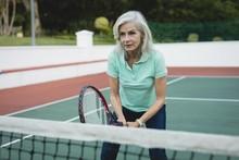 Senior Woman Playing Tennis In Tennis Court