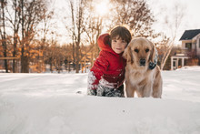 Portrait Of A Boy Sitting In Snow With His Golden Retriever Dog