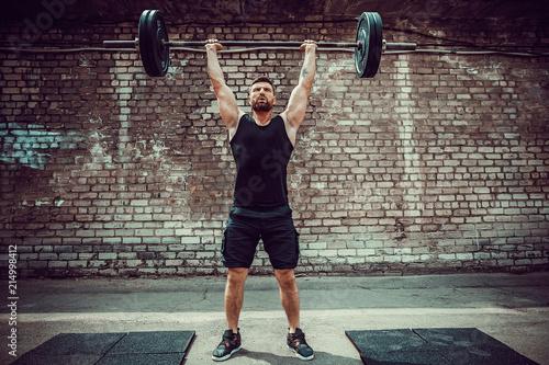 Fényképezés  Muscular fitness man doing deadlift a barbell over his head in outdoor, street gym