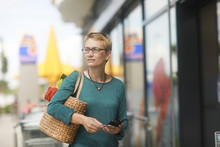 Woman Standing Outside A Supermarket Holding Her Mobile Phone And Credit Card