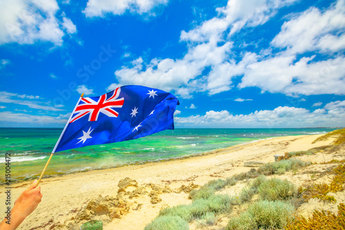 Foto op Canvas Australië Australian flag waving on the foreground with coastal landscape of Mettams Pool, Trigg Beach, North Beach near Perth in Western Australia. Tourism in Australia.
