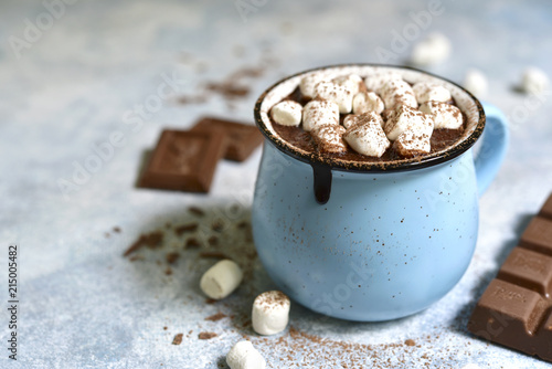 Homemade hot chocolate with mini marshmallow in a blue enamel mug.Rustic style.