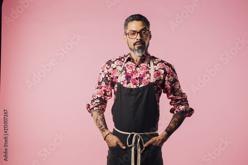 Portrait Of A Stylish Cook With Tattoos And Apron Isolated On Pink
