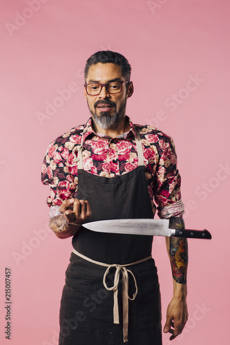 Fotografie, Obraz  A chef and his sharp knife/Portrait of a man in apron balancing a big steak knif