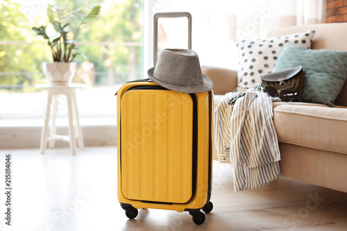 Bright yellow suitcase packed for journey and hat at home