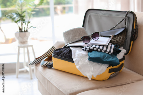 Fototapeta Open yellow suitcase with different clothes packed for journey at home