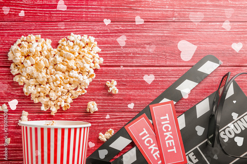 Flat lay composition with tasty popcorn, tickets and clapboard on red wooden background. Cinema evening
