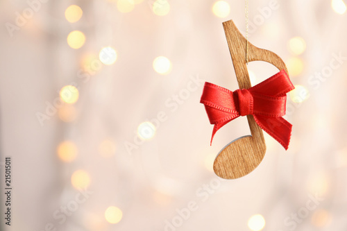 Wooden note with bow against blurred lights. Christmas music concept