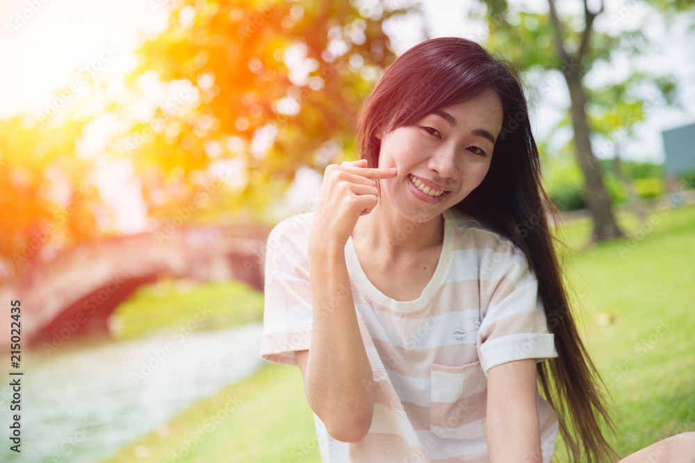 Valokuva  Cute asian woman smile with finger dimples cheek in the park