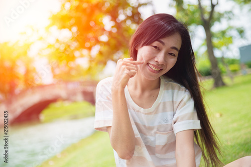 Cute asian woman smile with finger dimples cheek in the park Fototapet