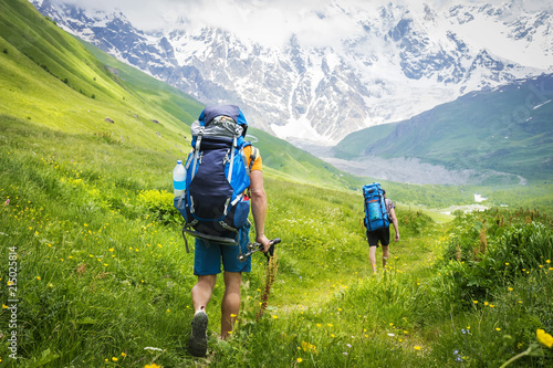 Tourists with backpacks on hiking trail walk along green hills in highlands. Hiking in mountains. group of tourists hike to mountain. Leisure. Holidays in mountains. Adventures in Caucasus