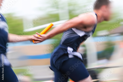 Fotografie, Obraz  Motion blurred relay race at a track and field event