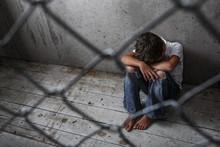 Depressed Young Boy Sitting Al...
