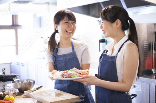 Fototapeta 出来上がった料理を持ち微笑みあう二人の女性 obraz