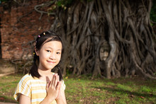 Asian Cute Girl With Respecting Or Pray, Buddha Head Entwined With Tree Roots Backgrund,Wat Mahathat,Ayutthaya Province,Thailand
