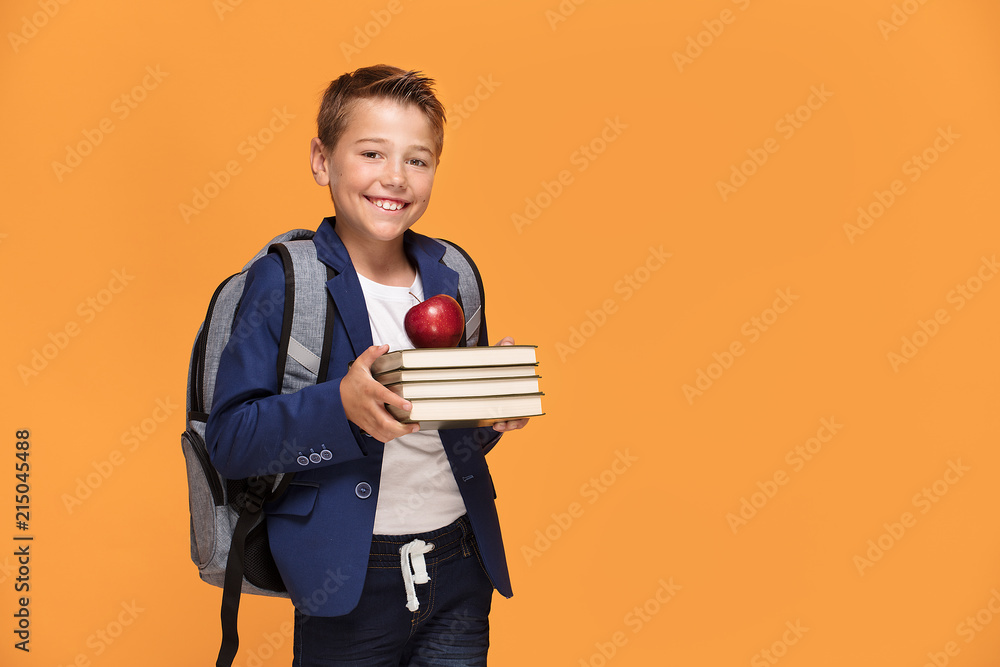 Fototapety, obrazy: Little school boy with backpack and books.
