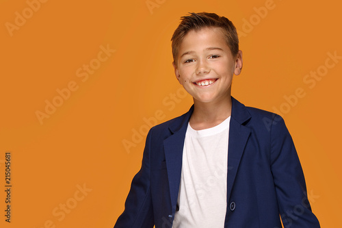 Fotografie, Obraz  Little elegant boy smiling on orange background.