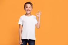 Young Emotional Little Boy On Orange Studio Background.