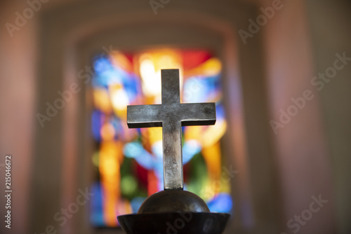Foto A dim old church interior lit by suns rays penetrating through a colorful staine